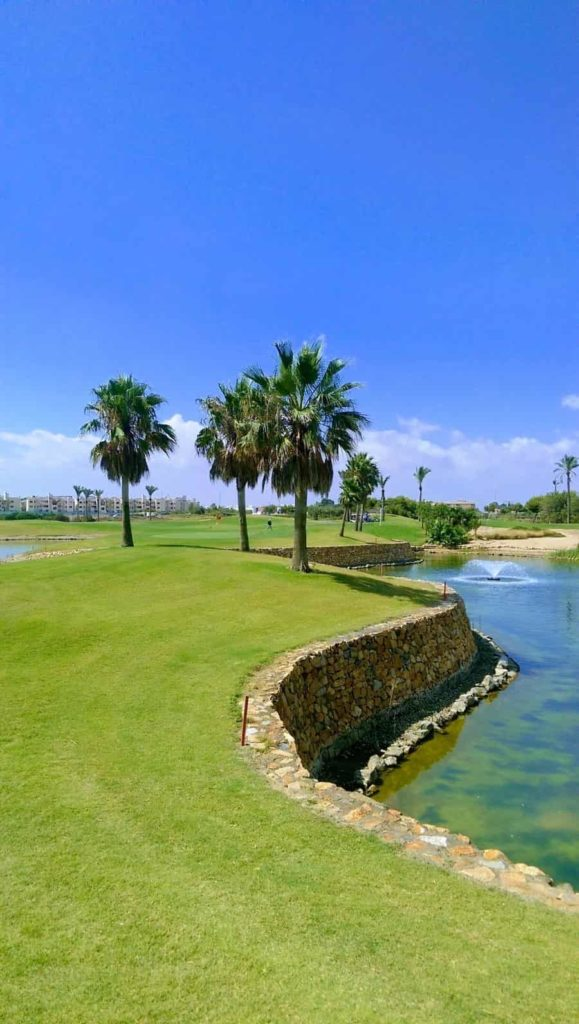A view of Roda Golf 12th green with water front and back