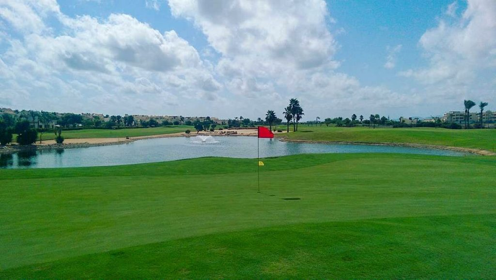 13th green of the Roda Golf Course with water to the right and bunkers left